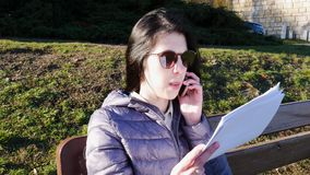 Education concept. A young woman in sunglasses teaches a lecture aloud on the bench and speaking by mobile phone stock video footage