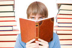 Education conceptual image. Young boy reading and studying between books Royalty Free Stock Photo