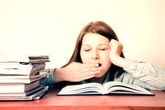 Education conceptual image. Young tired girl yawns during doing her homework Royalty Free Stock Photos