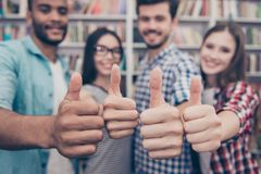 Education is cool! Is success, future and leadership. Cropped cl. Ose up shot of four attractive young international bachelors in library, gesturing thumb ups stock images