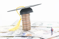 Education Cost. Miniature student looking at the mortarboard on top of a stacked of coins close up stock images