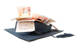 Education costs. Pile of British banknotes inside a graduation cap Royalty Free Stock Image
