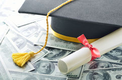 Education costs. Graduation hat with diploma and money Stock Photos
