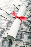 Education costs. Graduation diploma on background of US dollar bills Stock Photos