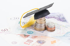 Education costs. Mortarboard on british coins and pounds sterling banknotes close-up stock image