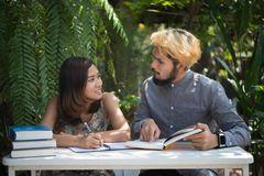 Education couple sitting at nature home garden, time to reading. And tutorial for exam together. Education people concept royalty free stock photography
