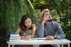 Education couple sitting at nature home garden, time to reading. And tutorial for exam together. Education people concept stock photo