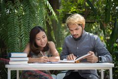 Education couple sitting at nature home garden, time to reading. And tutorial for exam together. Education people concept royalty free stock image
