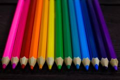 Education and creativity concept: colored pencils on wooden background royalty free stock images