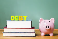 Education debt them with textbooks and piggy bank Royalty Free Stock Image