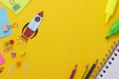 Education development concept. Back to school. Yellow background withschool supplies, notebook, rocket and sticky notes. Mock up.