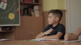 Education, elementary school. Learning and people concept - group of school kids with pens and notebooks writing test in stock footage