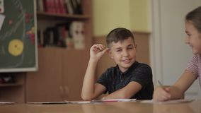 Education, elementary school. Learning and people concept - group of school kids with pens and notebooks writing test in. Classroom stock footage