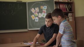 Education, elementary school. Learning and people concept - group of school kids with pens and notebooks writing test in. Classroom stock video footage