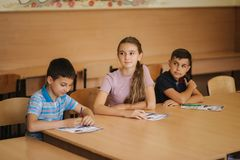 Education, elementary school. Learning and people concept - group of school kids with pens and notebooks writing test in. Education, elementary school, learning stock photography
