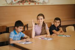 Education, elementary school. Learning and people concept - group of school kids with pens and notebooks writing test in. Education, elementary school, learning royalty free stock images