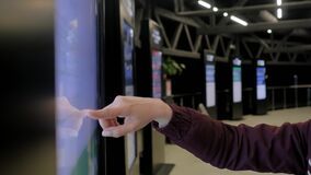 Woman hand using touchscreen display of interactive kiosk at exhibition