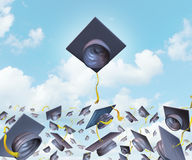 Education Excellence. And higher learning success with graduation hats thrown in the air as a celebration with a leading mortar board higher than the Royalty Free Stock Images