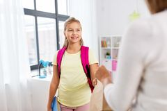 Student girl getting school lunch from mother stock photo