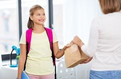 Student girl getting school lunch from mother stock images