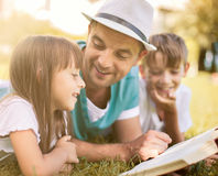 Education, family concept. Father reading a book to his children while laying outdoor on the grass in the park Stock Photography