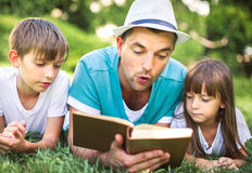 Education, family concept. Father reading a book to his children while laying outdoor on the grass in the park stock photo