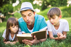 Education, family concept. Father reading a book to his children while laying outdoor on the grass in the park stock image