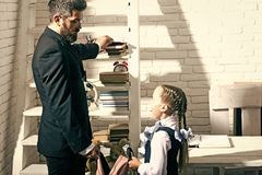 Education and family concept. Man and kid stand by shelf. With school supplies. Daughter and father in classroom on white brick background. Schoolgirl and dad stock image