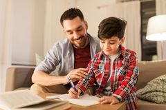 Father and son doing homework together. Education, family and homework concept - happy father and son with book writing to notebook at home stock photo