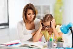 Mother helping daughter with difficult homework royalty free stock photo