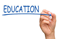 Education - female hand with blue marker writing text. On white background stock images
