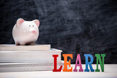 Education financial saving. Pink Piggy bank on top of books with Stock Photos