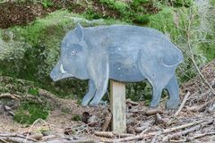 Education in the forest - wooden wild boar waiting to be spotted royalty free stock photo