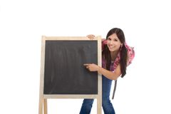 Education - Friendly Hispanic woman high school. Education - Latina college student with backpack pointing to Copy space board Royalty Free Stock Images