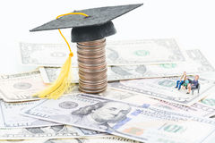 Education Fund. Miniature parents and their child besides the mortarboard on top of a stacked of coins close up Stock Image