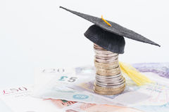 Education fund. Mortarboard on british coins and pounds sterling banknotes close-up royalty free stock photo