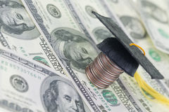 Education fund. Mortarboard on top of a stack of quarters and American dollars banknote background