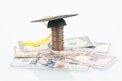 Education Fund. Mortarboard on top of a stacked of coins close up stock photography
