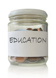 Education funds. Glass jar filled with coins labeled with education Royalty Free Stock Photography