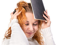 Education - girl holds a notebook on her head Royalty Free Stock Photo