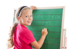 Education girl writing on blackboard. A little girl in school writing on a blackboard Stock Photography