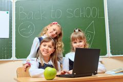 Education girls. Happy schoolchildren at a classroom during the lesson. Education Stock Photo