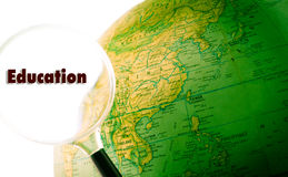 Education Globe. A green globe with a magnifying glass looking at the word education royalty free stock image