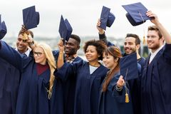 Happy graduates or students waving mortar boards Royalty Free Stock Photos