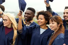 Happy graduates or students waving mortar boards Royalty Free Stock Images
