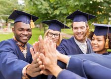 Happy students in mortar boards making high five Stock Photography
