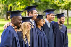 Happy students or bachelors in mortar boards Royalty Free Stock Images