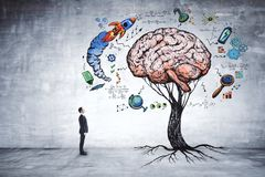 Education, growth, brainstorm and startup concept. Businessman looking at abstract brain tree in concrete interior. Education, growth, brainstorm and startup Royalty Free Stock Photos