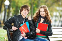 Education and students. Happy young college student with notebooks on bench. Education. Happy college boy and girl students with workbook and notebook sitting on Royalty Free Stock Photography