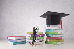 Education and hard work concept. Businessman on ladder trying to reach mortarboard placed on abstract colorful book ladder on concrete background. Education and stock images